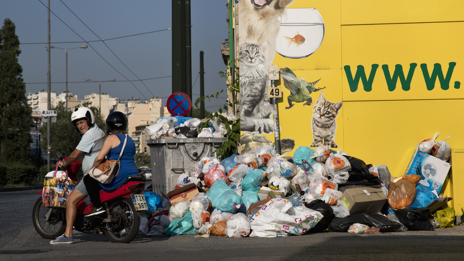 A motorcyclist looks on as he drives next to a pile of garbage in Piraeus, near Athens, on Monday, June 26, 2017. Municipality workers have been on strike for almost a week , hindering trash collection across the country. (AP/Petros Giannakouris)