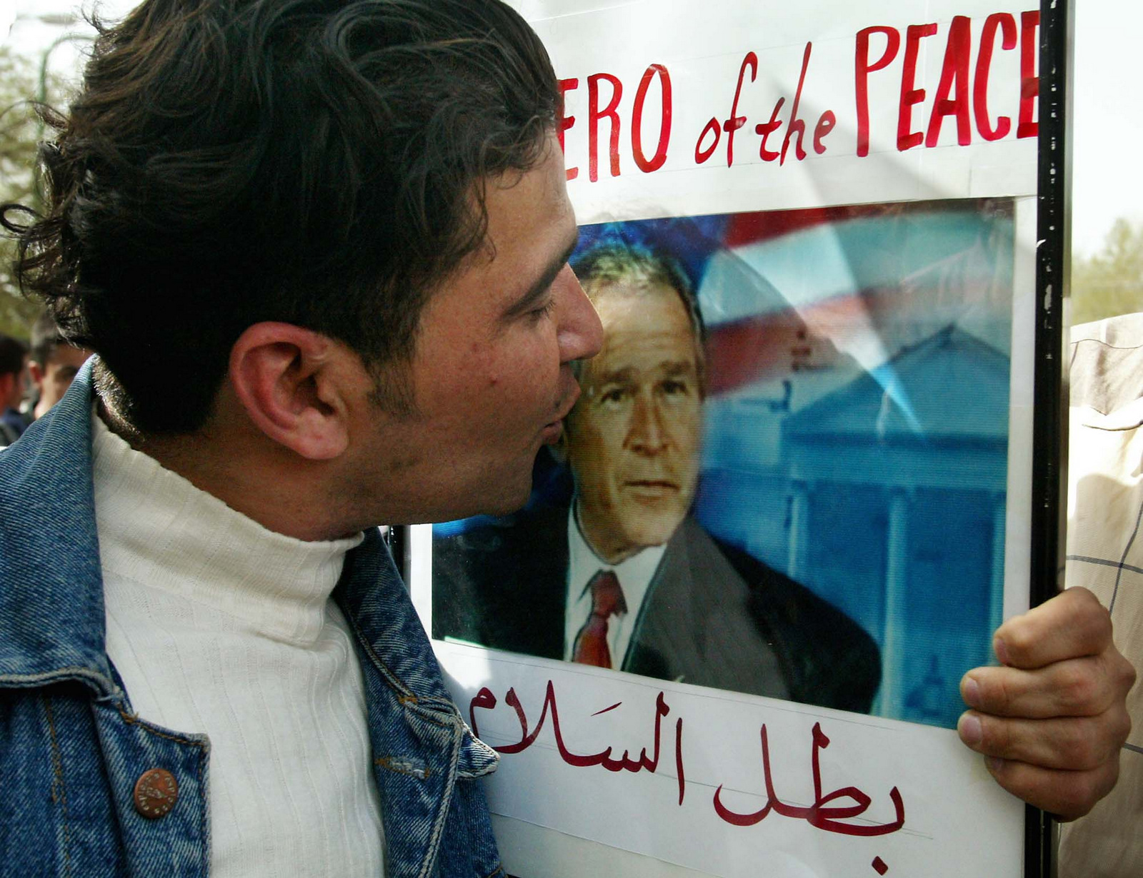 A Kurd kisses a picture of United States President George W. Bush during celebrations in the streets of Sulaymaniyah, northern Iraq Wednesday April 9, 2003. (AP/Kevin Frayer)