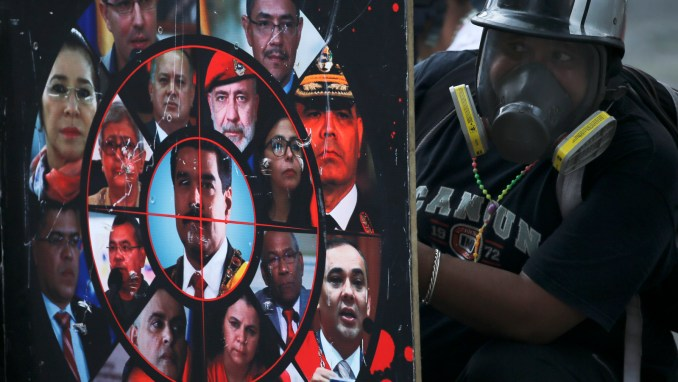 An anti-government protester holds a shield brandished with photos of President Nicolas Maduro, government officials and a gun sight, during clashes with security forces in Caracas, Venezuela, July 22, 2017. (AP/Fernando Llano)