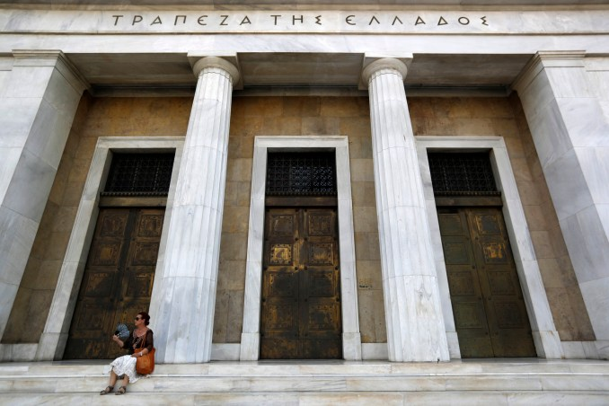 A woman uses her fan to cool down outside the Bank of Greece headquarters in Athens, July 24, 2017. (AP/Thanassis Stavrakis)