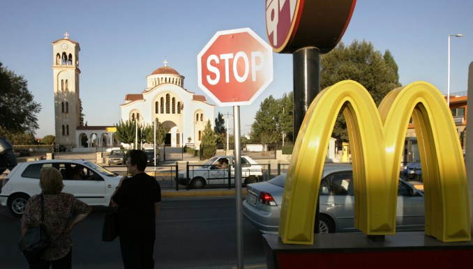 Greek commuters stand near a McDonald's restaurant in Marathon, Greece. (AP/Lefteris Pitarakis)