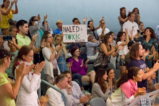 Demonstrators cheer at a city commission meeting in Miami Beach, Fla. Opponents want to stop the aerial spraying of the insecticide naled, used to combat the Aedes aegypti mosquito, Sept. 14, 2016. (AP Photo/Wilfredo Lee)