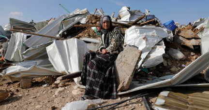 A Bedouin woman sit on the remnants of her demolished home in the Bedouin village of Umm al-Hiran, near the southern city of Beersheba, Israel, Jan. 18, 2017. (AP/Tsafrir Abayov)