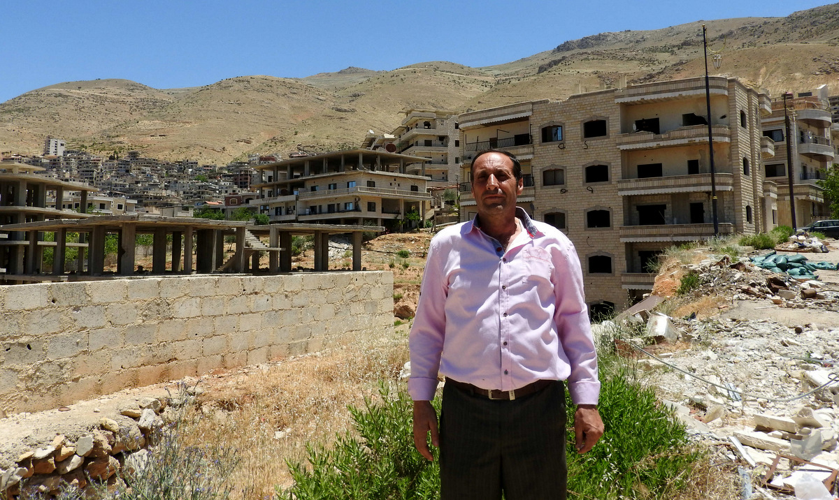 """The Mayor of Madaya, standing near buildings once occupied by """"moderate rebels"""" who sniped and fired mortars on the road below."""