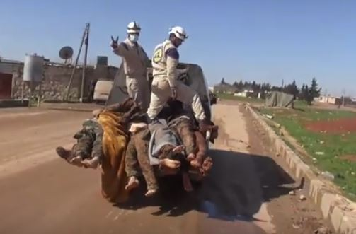 Screenshot from video showing White Helmets standing on top of Syrian Arab Army soldiers bodies, whose boots have been stolen or removed.