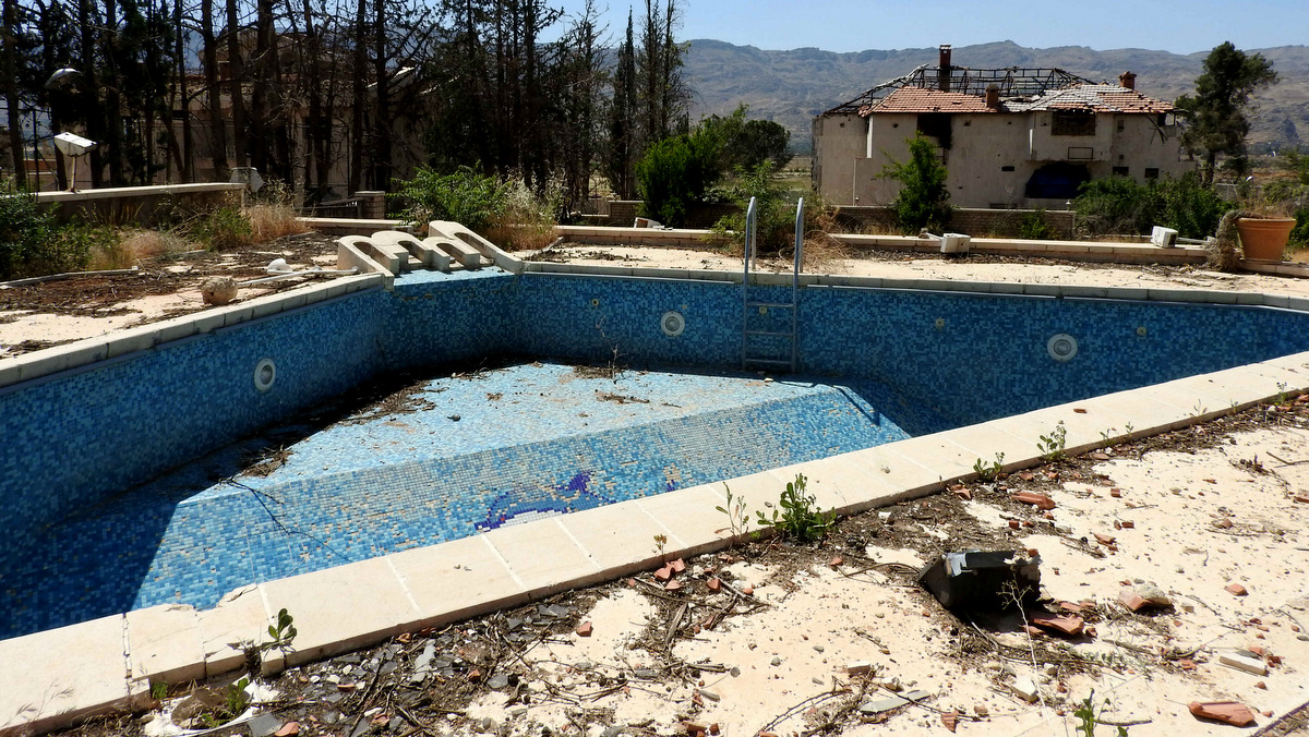 The outside of a villa used by rebels as a tunnel entrance. The idyllic mountain view was marred only by the signs of battle: an empty swimming pool lightly littered with rubble, and a villa beyond, roof and walls blown out by shelling. (Photo: Eva Bartlett/MintPress News)