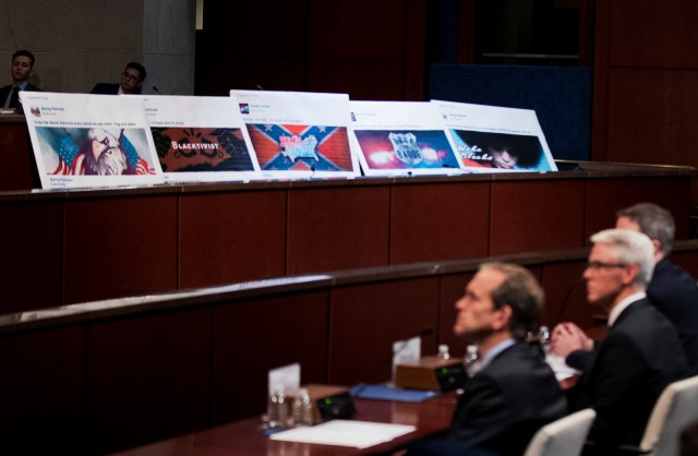 Facebook ads linked to a purported Russian effort to disrupt the American political process are displayed as, from left, Google's Senior Vice President and General Counsel Kent Walker, Facebook's General Counsel Colin Stretch, and Twitter's Acting General Counsel Sean Edgett, testify during a House Intelligence Committee hearing on Capitol Hill in Washington, Nov. 1, 2017. (AP/Manuel Balce Ceneta)