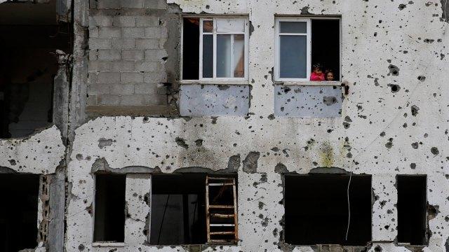Palestyńskie dzieci wyglądają przez okno w części uszkodzonego bloku mieszkalnego, który został częściowo zniszczony przez Izrael w 2014 r. W Beit Lahiya, Strefa Gazy, 22 lutego 2016 r. Hatem Moussa |  AP