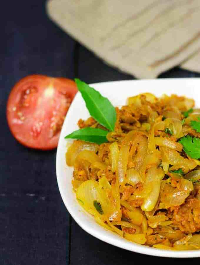 Besan Pyaaz Ki Sabzi on a white bowl full of besan pyaaz ki sabji and garnished with curry leaves kept on a dark wooden surface with and handkerchief on the background