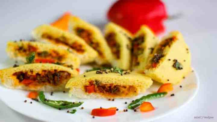 Bread dhokla sandwich on a white plate cutted into pieces in half and tempering of mustard seed and chilli with few strings of curry leaves