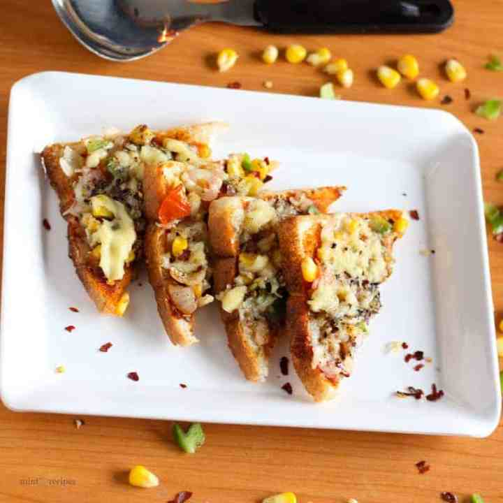 Bread pizza on a black plate with some pieces of bread pizza garnished with some oregano and chilli flakes kept on wooden surface