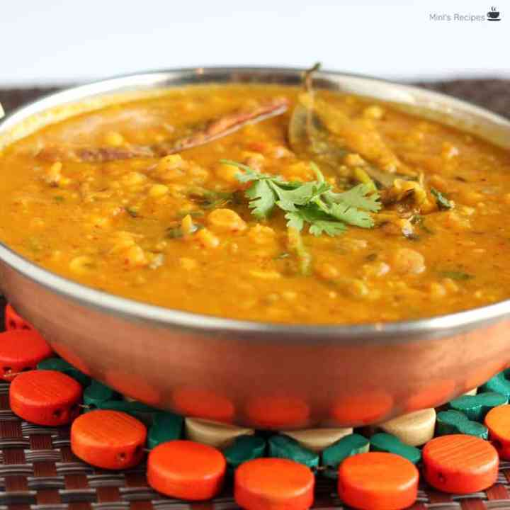 Dal fry on a heavy vessel kept on a wooden stand with a big spoon besides it
