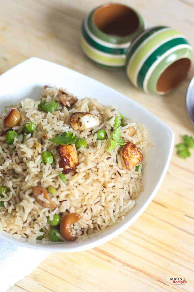 Matar paneer pulao in a white bowl with some coriander leaves kept on a wooden surface with top wooden bowlsin the background |
