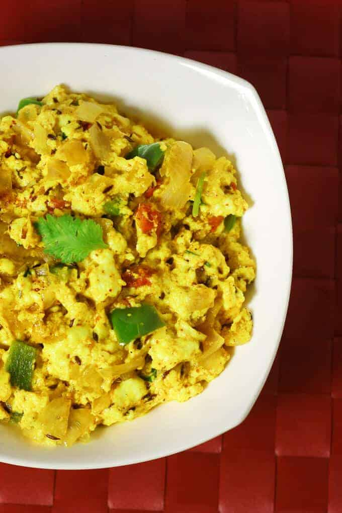 Paneer Bhurji on a white bowl kept on a red color mattress with some garnishing of coriander leaves |