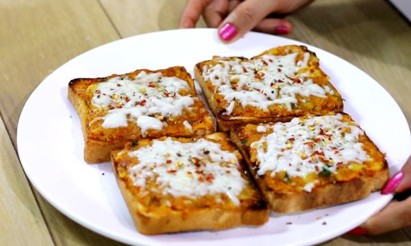 Potato cheese toast on a white plate with some potato mixture and grated cheese with some italian seasoning and red chilli flakes| www.mintsrecipes.com |