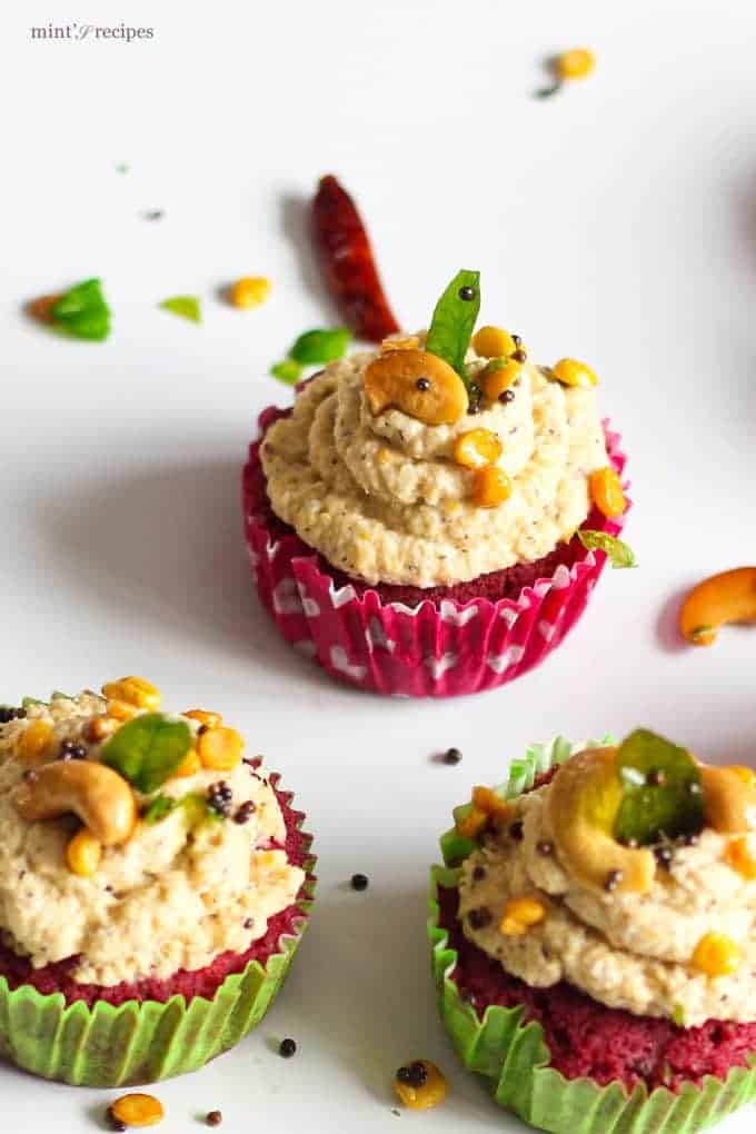 Red Velvet Idli Cupcake on a white surface with tempering of coconut chutney and little temmpering of curry leaves, mustard seed, chana dal and cashew |