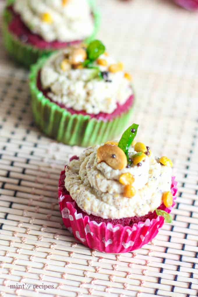 Red Velvet Idli Cupcake on a white surface with tempering of coconut chutney and little tempering of curry leaves, mustard seed, chana dal and cashew |