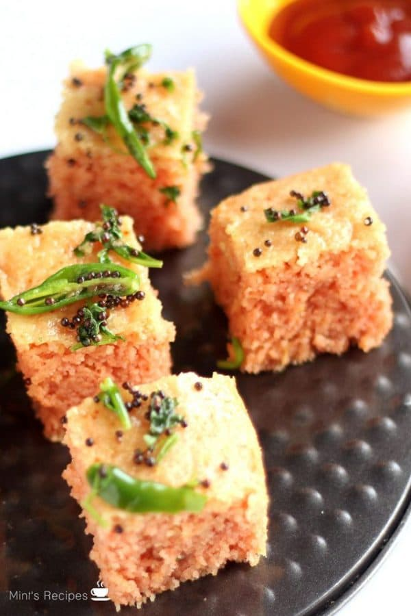 Suji Dhokla on a black plate with some tempering of green chili and mustard seed with some tomato ketchup on the background