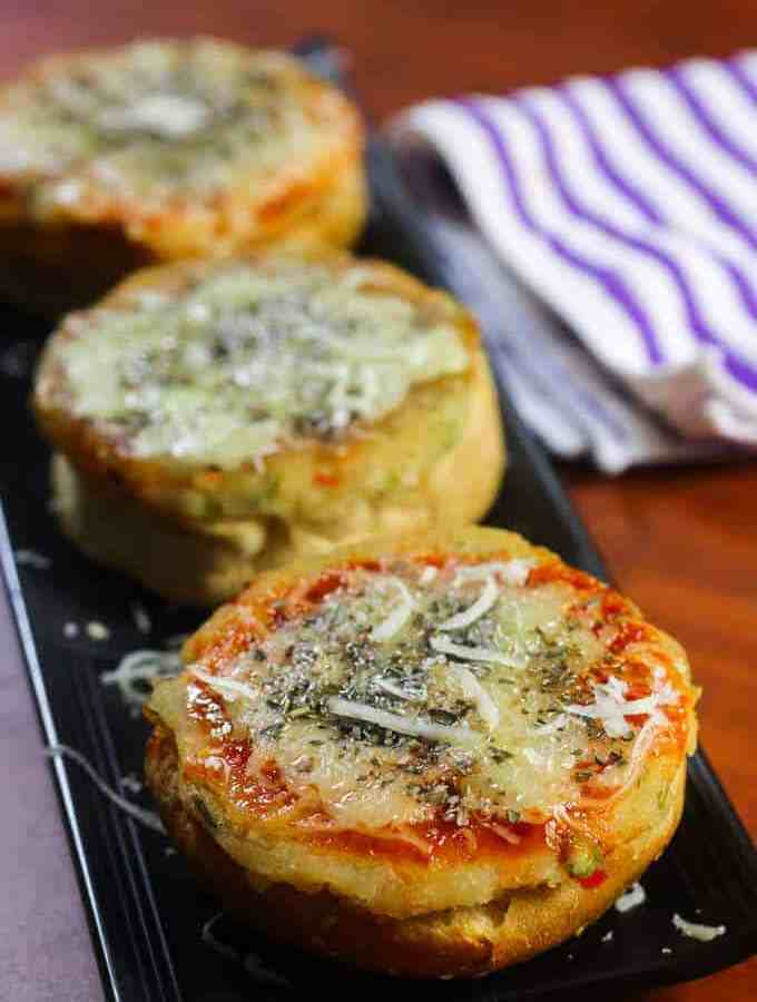 Veg Suji Buns on a black tray with some suji buns garnished with some cheese and oregano kept on a wooden surface  