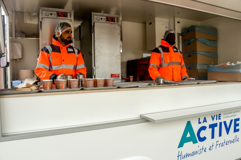Des membres de l'association Vie Active, mandatée par l'Etat, se préparent pour la distribution de repas aux migrants de Calais, le 6 mars 2018