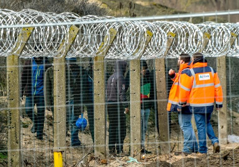 Des membres de l'association Vie Active, mandatée par l'Etat pour la distribution de repas, parlent avec des migrants à travers un grillage surmonté de barbelés, le 6 mars 2018 à Calais