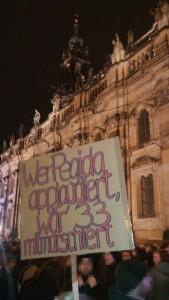 """Plakat mit Aufschrift """"Wer Pegida applaudiert, wär' 33 mitmarschiert"""" auf der """"Dresden für alle""""-Demonstration am 15.12.2014."""