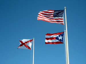 U.S. flag, Puerto Rican Flag, and Burgundy Cross, representing Spanish influence