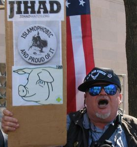 "A man holding a sign saying ""Islamophobic and proud of it"". https://goo.gl/ww7TtU"