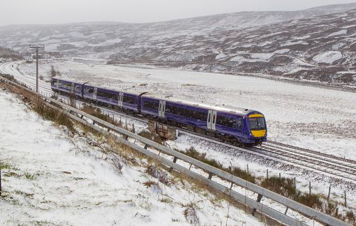 A train surrounded by snow covered hills in the Cairngorms National Park
