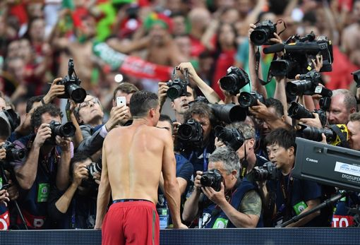 PARIS, FRANCE - JULY 10: Cristiano Ronaldo of Portugal is centre of media attention as he celebrates winning at the final whistle during the UEFA EURO 2016 Final match between Portugal and France at Stade de France on July 10, 2016 in Paris, France. (Photo by Michael Regan/Getty Images)