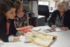 Carla Garapedian, left, shows the Mugerditchian manuscript to USC Shoah Foundation writer Robin Migdol, center, and Diana Hekimian