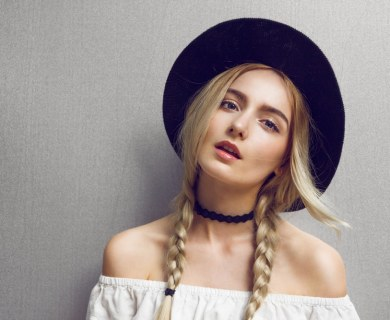 blonde, hip, girl with braids and a black hat. Her off the shoulder blouse accentuates her decolletage