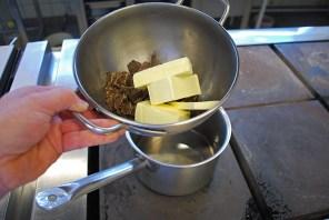 Wasser in einem Topf erhitzen. Gehackte Kuvertüre und die Butter darauf schmelzen lassen.
