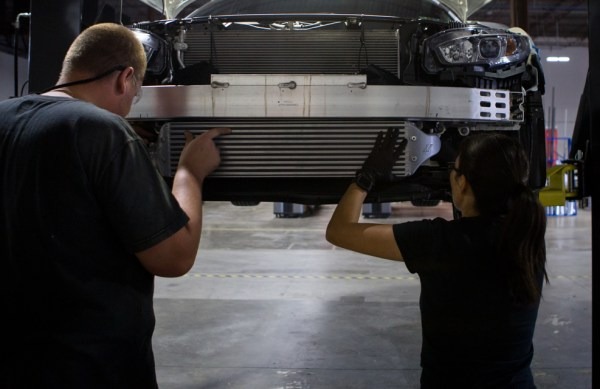 Ye, right, lends Dan a hand test fitting our intercooler sample into our loaner Si sedan.