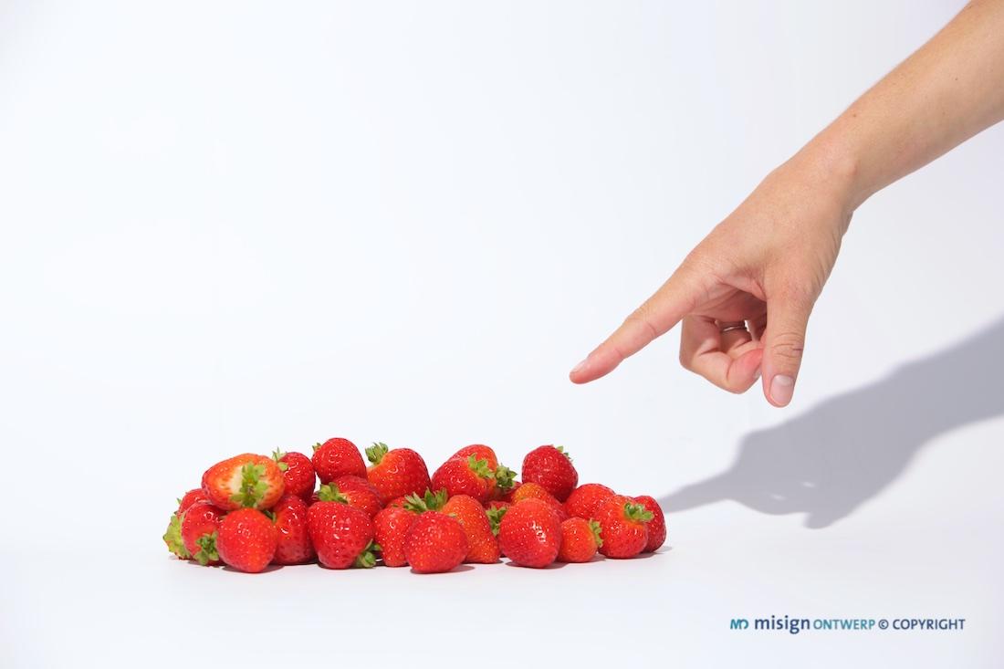 Een dameshand wijzend naar verse aardbeien op een witte achtergrond.