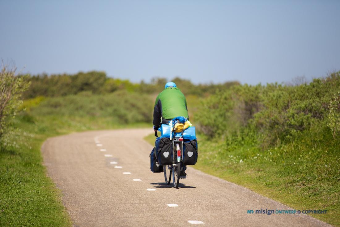 Fietser op fietsvakantie op een fietspad in de Noordwijkse duinen