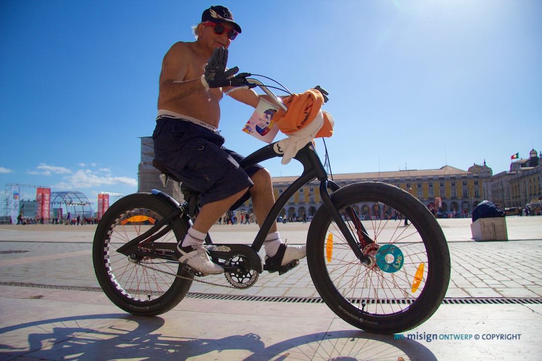 Oude man op een relaxte fiets op een zonnig plein in Lissabon, Portugal