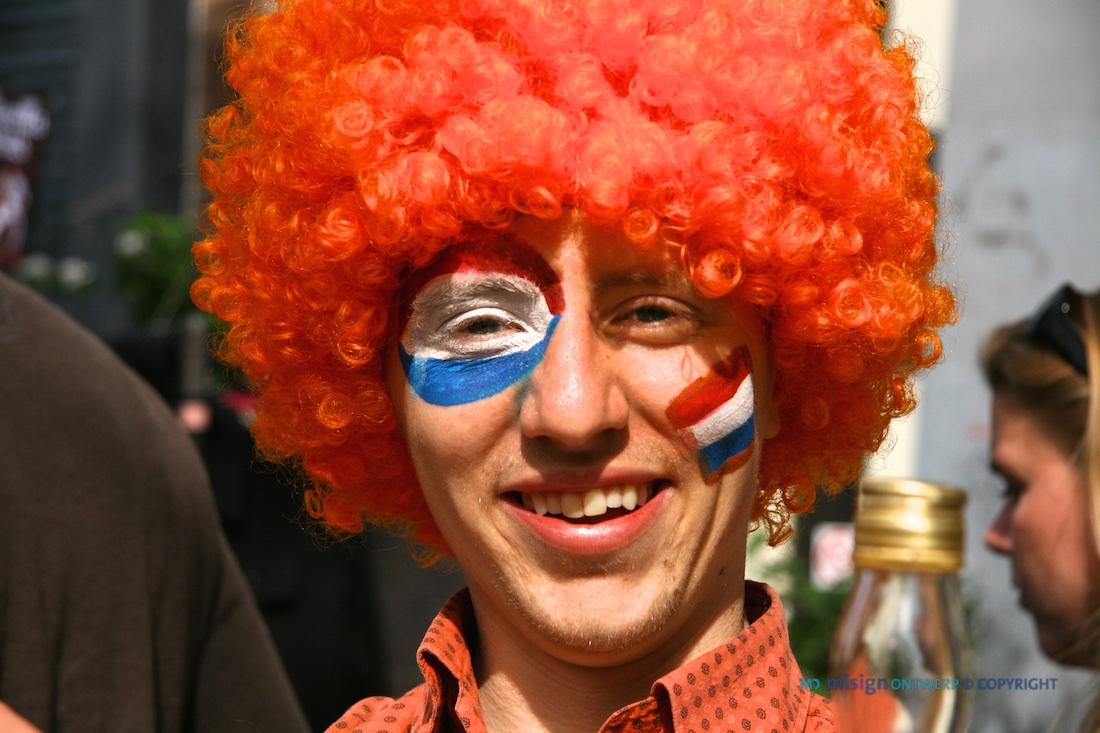 Lachende man met oranje pruik en Nederlandse vlag op zijn gezicht geschilderd tijdens koninginnedag 2010 in Amsterdam
