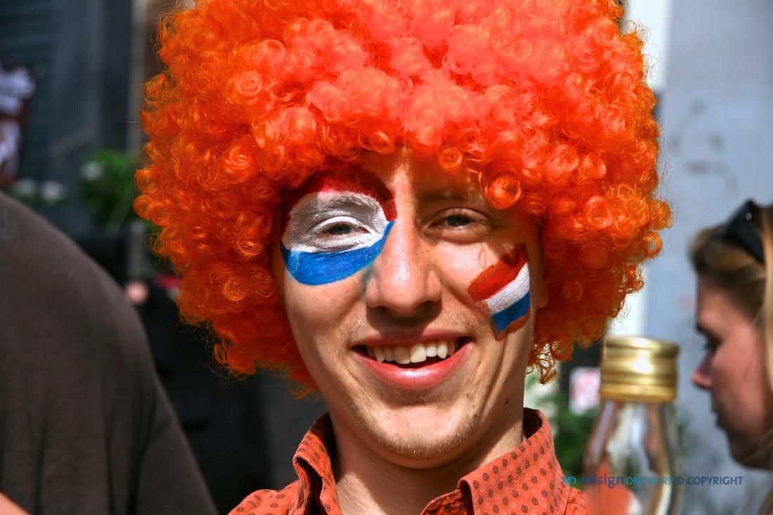 Lachende man met oranje pruik en Nederlandse vlagen op zijn gezicht geschilderd.