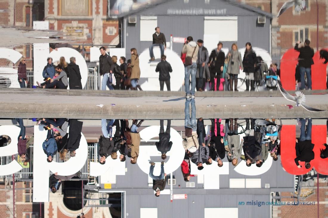 Toeristen in de reflectie van het water achter het Rijksmuseum in Amsterdam
