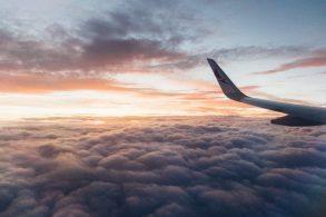 Ein Bild aus dem Flugzeug, wo man die Wolken, den Himmel und einen Flügel des Flugzeugs sieht