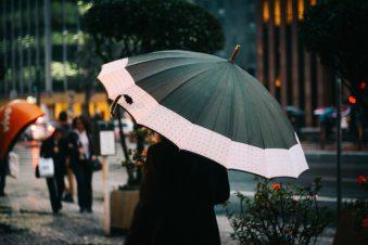 Eine Frau, die in einer Straße einen Regenschirm hält und damit ihren Kopf bedeckt