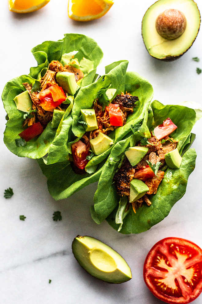 tacos in lettuce wraps with avocado and tomato on a white background