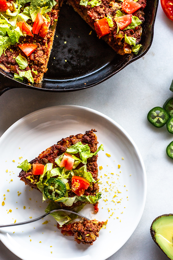 Whole30 Taco Skillet Pie sliced with lettuce, tomato, avocado and hot peppers on a white background.