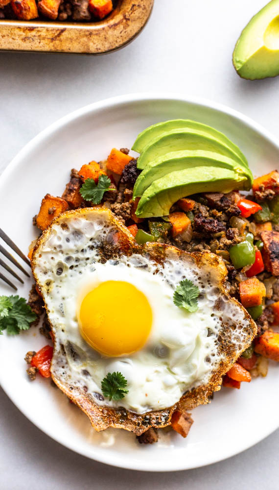 Looking for a better for you hash for breakfast (or whenever)? This Whole30 Bison Sweet Potato Hash has crispy sweet potatoes and veggies, lean bison and the perfect blend of spices.You can top with fried eggs, avocado, and cilantro for the best brunch or breakfast. This lower carb version can be made with turkey, beef, or venison, too. You make it on the stovetop and crisp it in the oven for the perfect potato. This recipe is #whole30approved and #paleo. #healthy #healthyrecipe #paleofood #breakfast