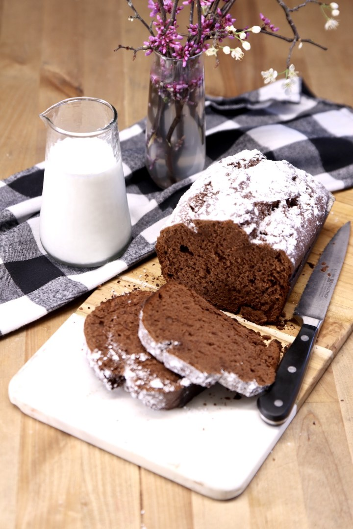 Chocolate banana bread with small milk jug and flowers