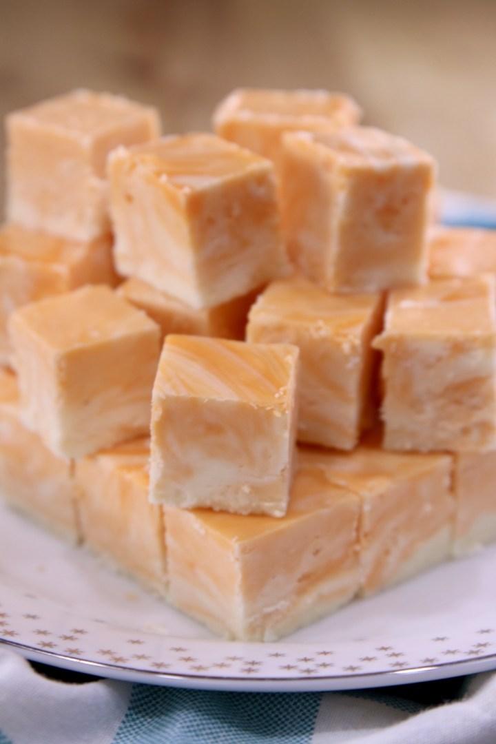 stack of orange cream marble fudge on a white plate