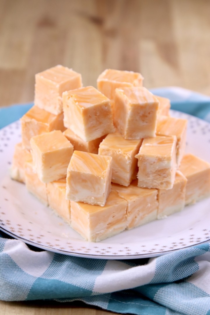 Squares of orange cream marble fudge stacked on a plate with blue and white check napkin