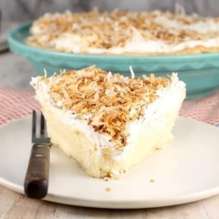 Coconut Cream Pie slice topped with whipped cream and toasted coconut