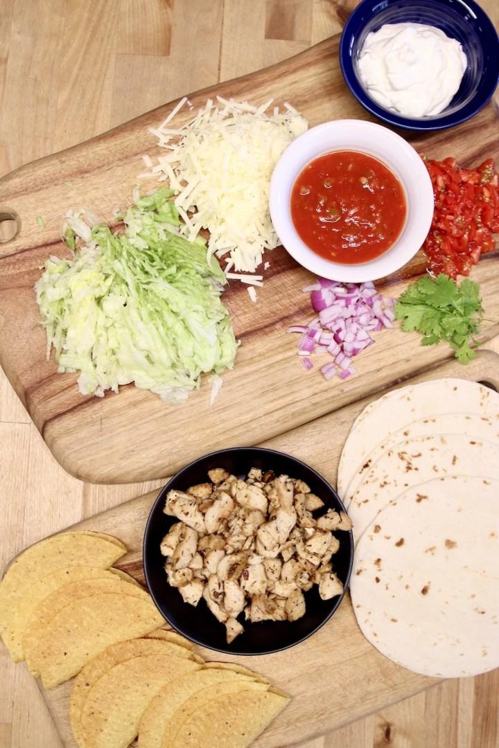 chicken tacos ingredients, lettuce, onion, cheese, salsa, chopped chicken, tortillas